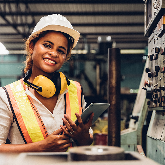 woman smiling with ipad working in factory industrial in front of board assessments